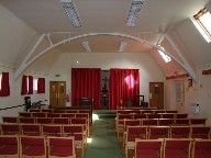 The interior, with its red flush curtains and red modern seating, is reminiscent of a small cinema.